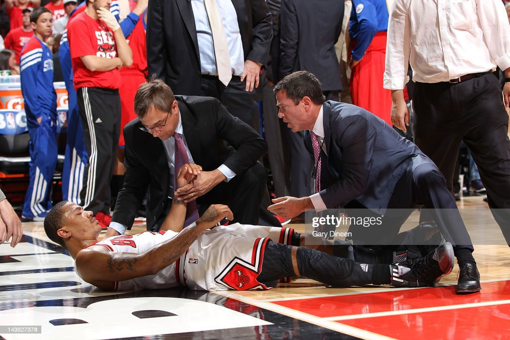 Chicago Bulls Head Athletic Trainer Fred Tedeschi helps Derrick Rose #1 after injuring his knee against the Philadelphia 76ers in Game One of the Eastern Conference Quarterfinals during the 2012 NBA Playoffs on April 28, 2012 at the United Center in Chicago, Illinois.