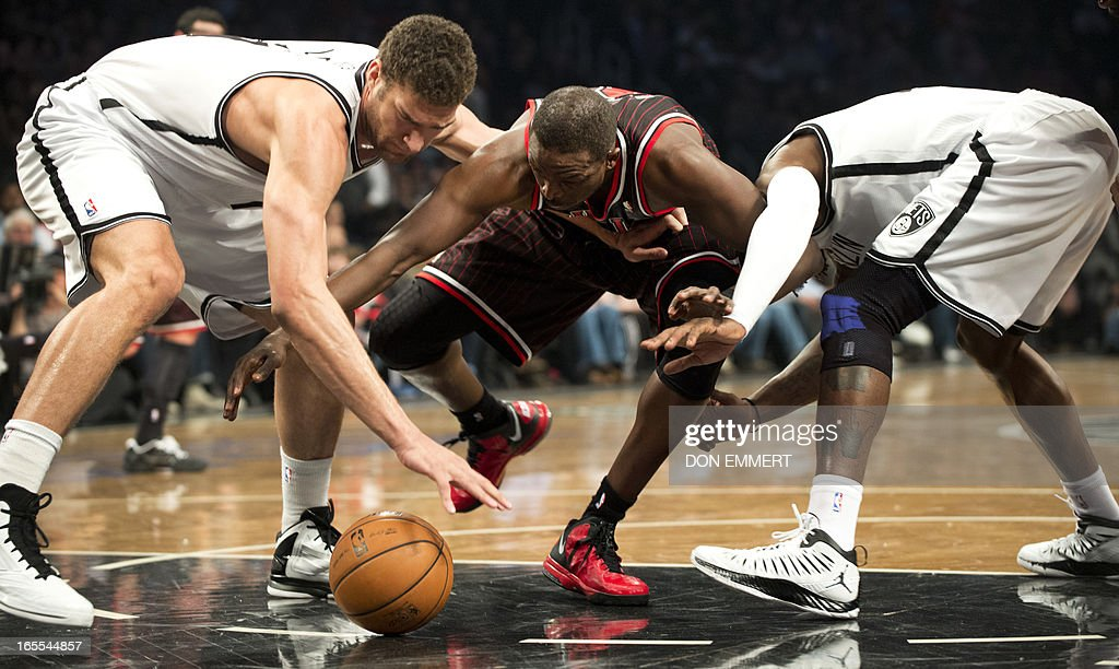 Chicago Bulls Luol Deng (C) fights for the ball with Brooklyn Nets Brook Lopez (L) and Gerald Wallace (R) during their NBA game April 4, 2013 at the Barclay Center in New York. AFP PHOTO/Don Emmert
