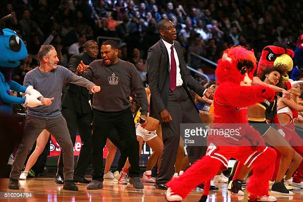 Chicago Bulls mascot Benny the Bull TV personality Jon Stewart actor Anthony Anderson and former NBA player Dikembe Mutombo dance on court in the...