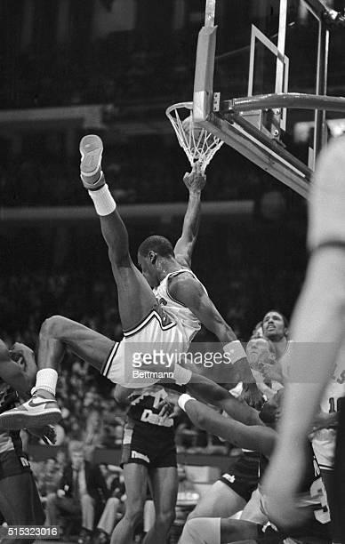 Chicago Bulls' Michael Jordan is headed for a crash landing on his backside despite his twofingered grasp on the net after a slam dunk during game...