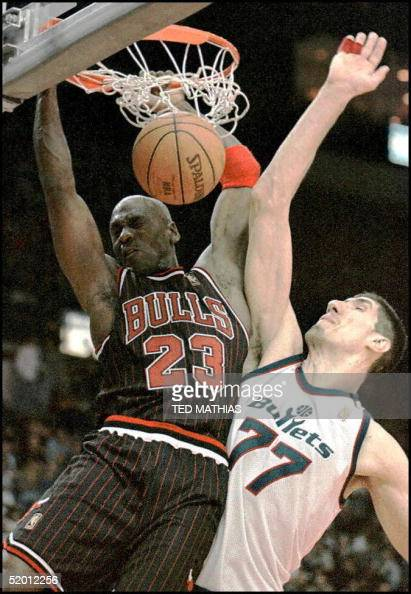Chicago Bulls Michael Jordan slams into Washington Bullets Gheorghe Muresan after making a basket in the fourth quarter in Landover MD 21 February...