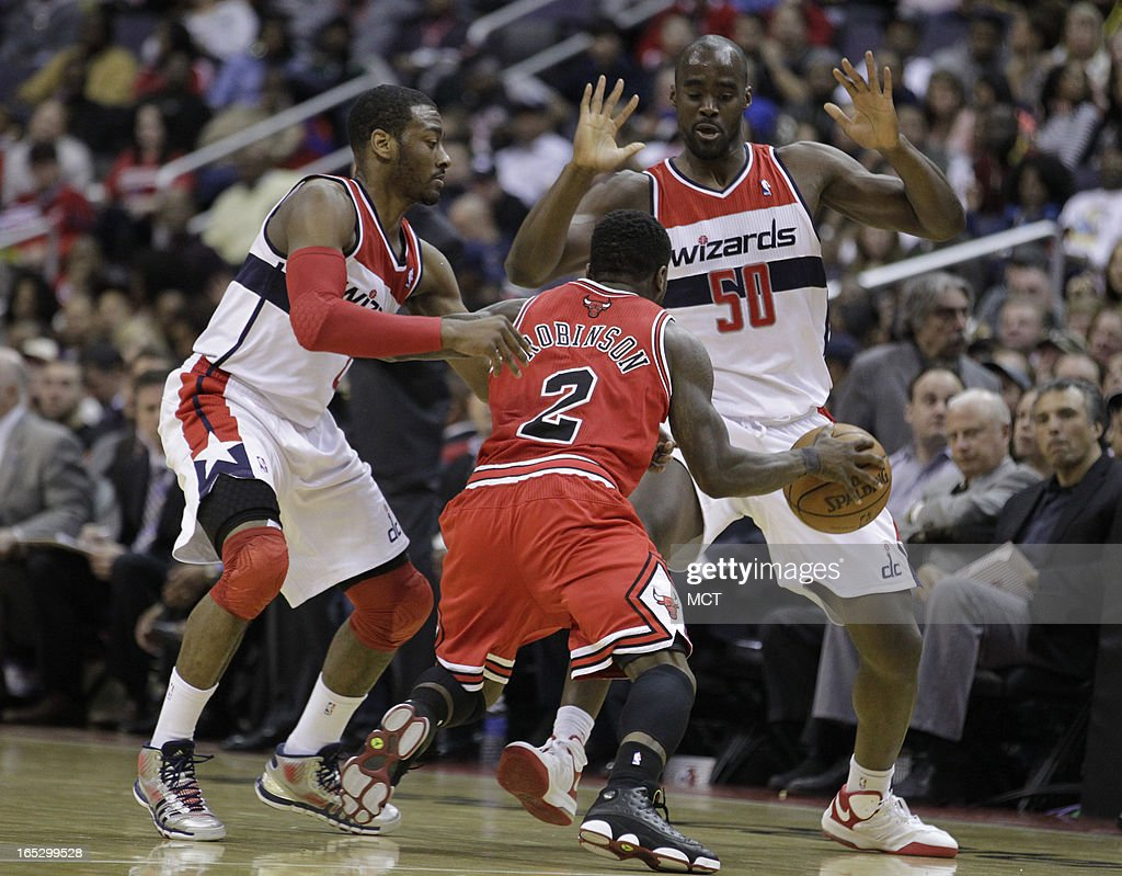 Chicago Bulls' Nate Robinson (2) moves the ball in between Washington Wizards' John Wall, left, and Emeka Okafor (50) in the second half at the Verizon Center in Washington, D.C., Tuesday, April 2, 2013.