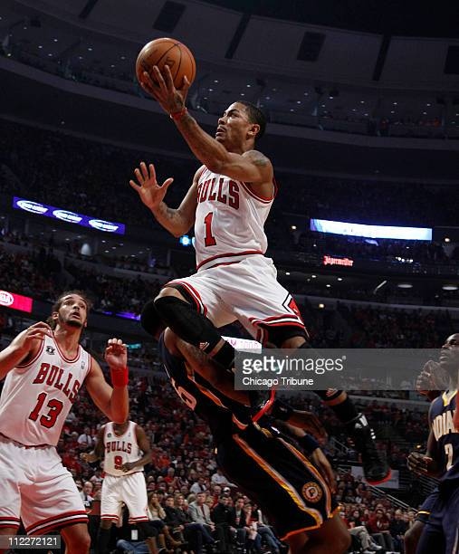 Chicago Bulls point guard Derrick Rose climbs over Indiana Pacers shooting guard Brandon Rush to make a basket during the first quarter of Game 1 of...