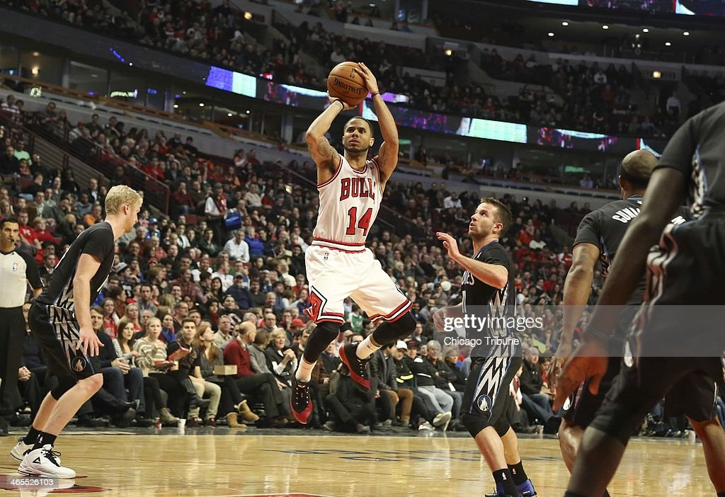 Chicago Bulls point guard D.J. Augustin (14) makes a basket in front of Minnesota Timberwolves point guard J.J. Barea (11) during the first half of their game at the United Center in Chicago on Monday, Jan., 27, 2014.