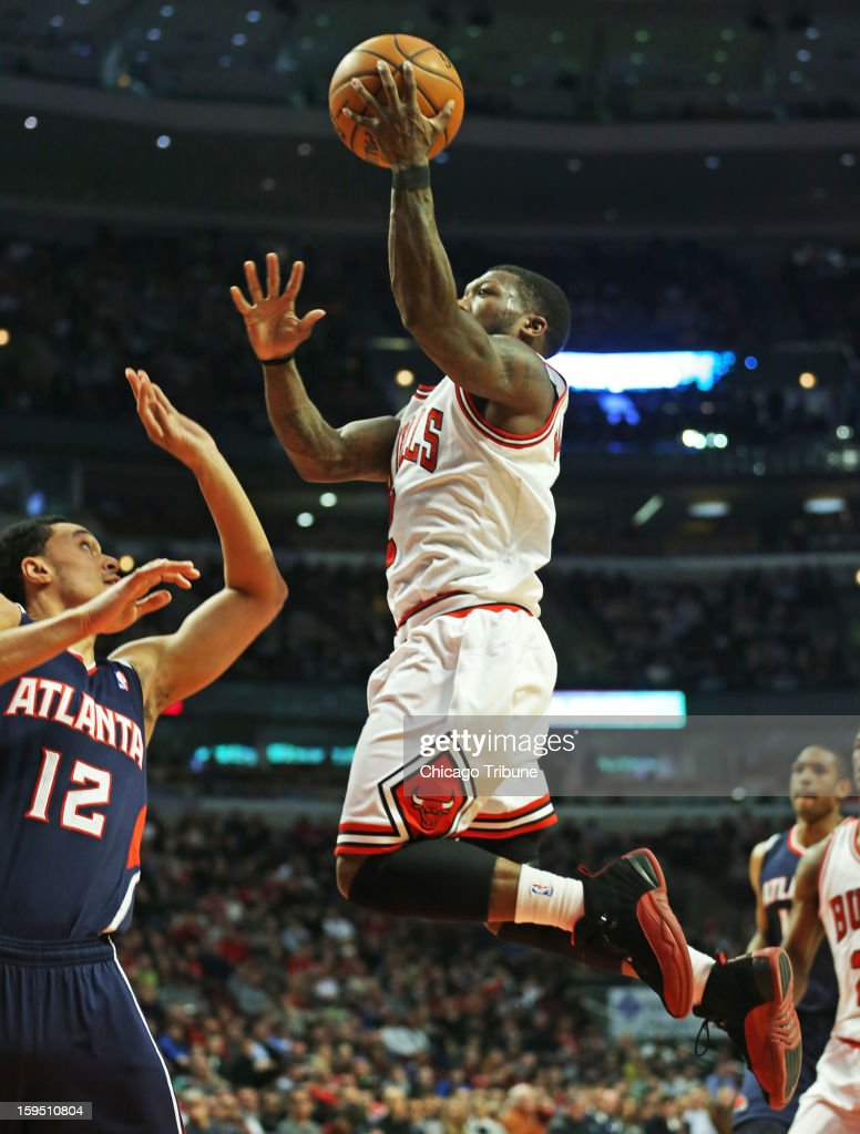 Chicago Bulls point guard Nate Robinson drives to the basket against Atlanta Hawks shooting guard John Jenkins during the first half of their game at...