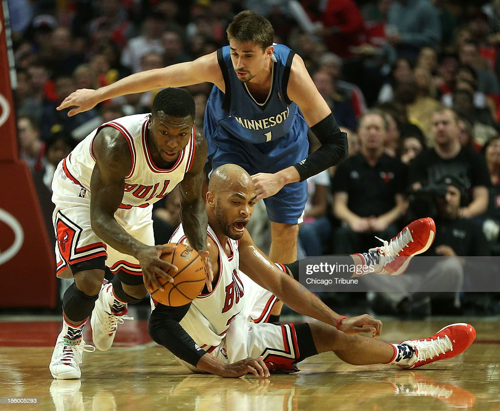 Chicago Bulls point guard Nate Robinson (2) picks up a loose ball in front of teammate Taj Gibson (22) and Minnesota Timberwolves point guard Alexey Shved (1) in the first half at the United Center in Chicago, Illinois, on Saturday, November 10, 2012.