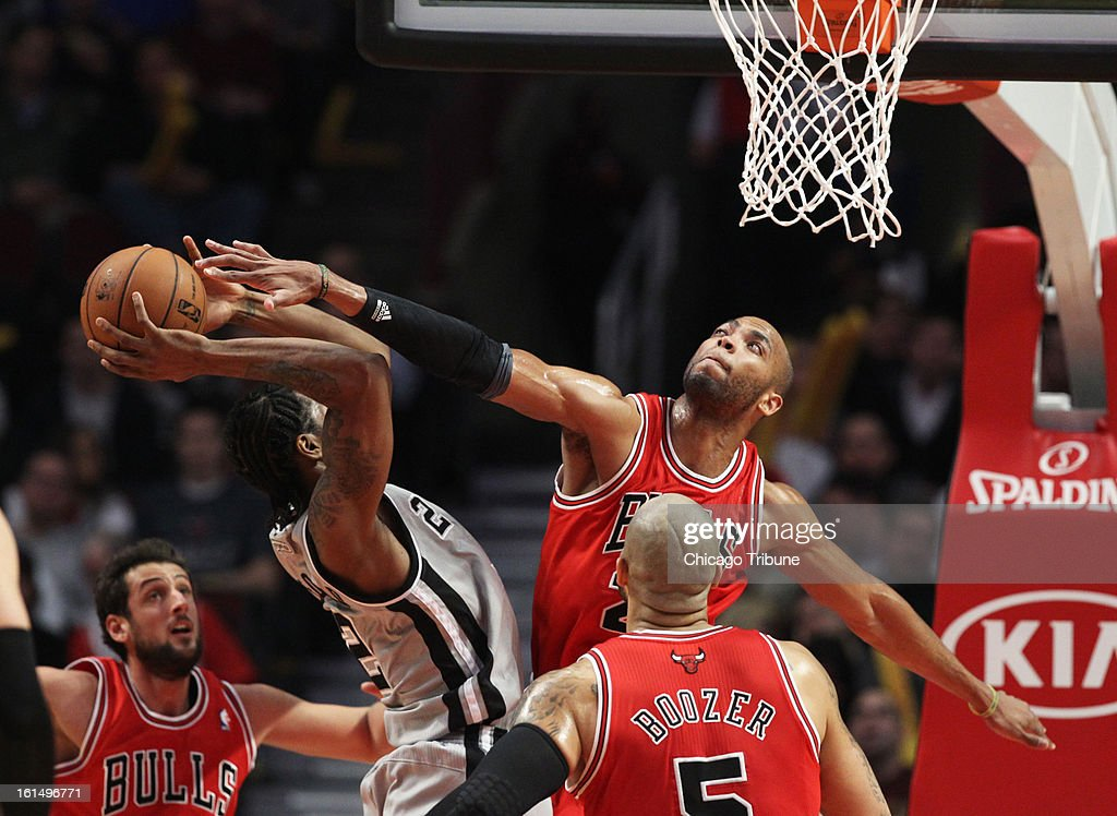 Chicago Bulls power forward Taj Gibson (22) stops San Antonio Spurs small forward Kawhi Leonard (2) during the first half at the United Center in Chicago, Illinois, Monday, February 11, 2013.
