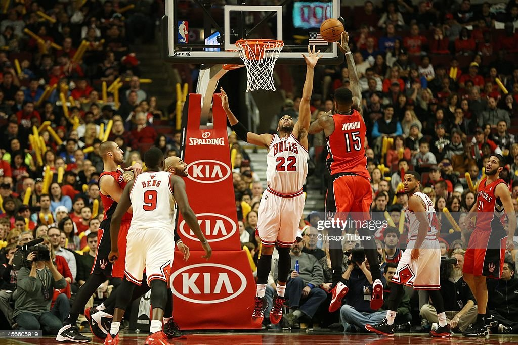 Chicago Bulls power forward Taj Gibson (22) tries to block a shot by Toronto Raptors power forward Amir Johnson (15) in the second half at the United Center in Chicago, Saturday, Dec. 14, 2013. The Raptors defeated the Bulls, 99-77.