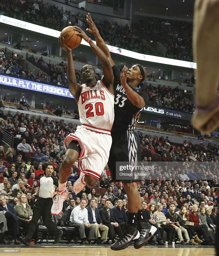 Chicago Bulls shooting guard Tony Snell (20), makes a basket past Minnesota Timberwolves power forward Dante Cunningham (33) during the first half of their game at the United Center in Chicago on Monday, Jan., 27, 2014.