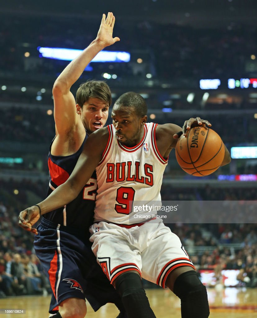 Chicago Bulls small forward Luol Deng (9) controls the ball against Atlanta Hawks shooting guard Kyle Korver (26) during the first half of their game at the United Center on Monday, January 14, 2013, in Chicago, Illinois.