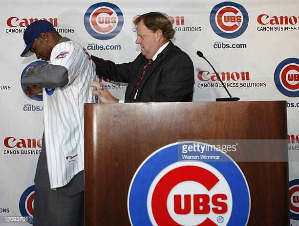 Chicago Cub General Manager Jim Hendry adjusts the jersey on Alfonso Soriano before Soriano is introduced to the Chicago media at the Stadium Club...