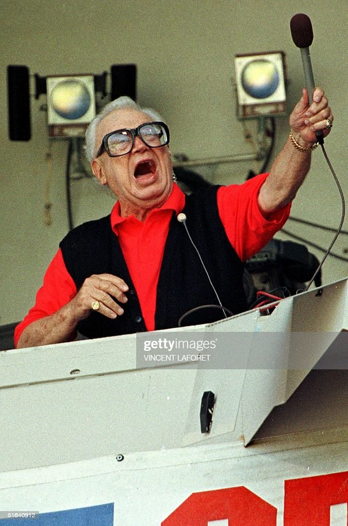 Chicago Cubs baseball announcer and Baseball Hall of Fame inductee Harry Caray conducts fans singing 'Take Me Out to the Ball Game' from his television booth during the seventh inning stretch in this 07 August 1997 file photo at Wrigley Field, Chicago, Il. Caray, who began his broadcasting career in 1941, died 17 February at a California hospital. He had collapsed 14 February while having Valentine's Day dinner with his wife.