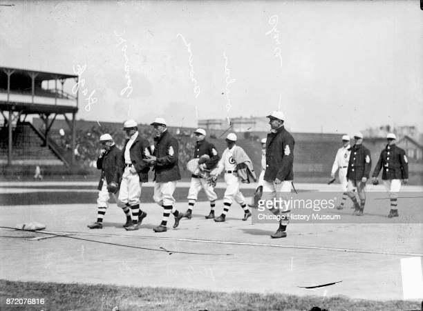Chicago Cubs baseball players walk off the field near second base during a game against the Cincinnati Reds at West Side Grounds Chicago Illinois...