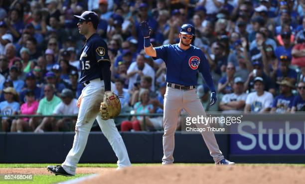 Chicago Cubs batter Ian Happ raises his arm at first base after driving in a run with a single in the second inning against the Milwaukee Brewers on...