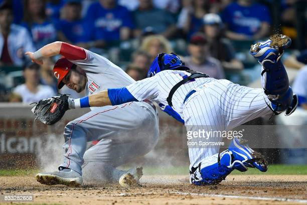 Chicago Cubs catcher Alex Avila tags out Cincinnati Reds left fielder Jesse Winker at home plate during the game between the Cincinnati Reds and the...