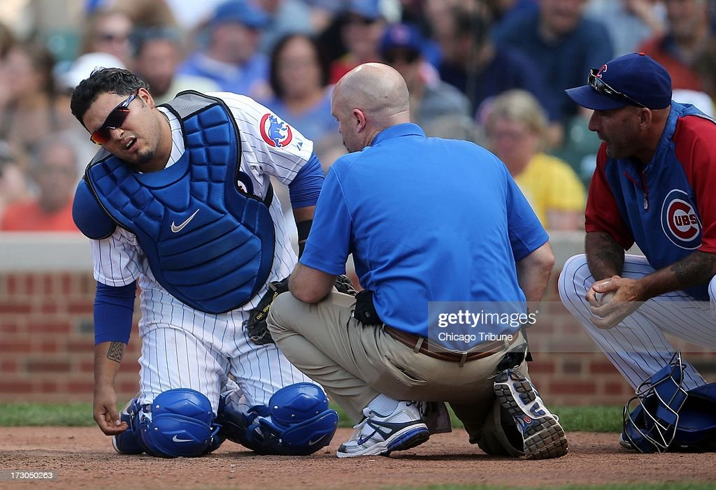 Chicago Cubs catcher Dioner Navarro receives medical attention after being shaken up in the eighth inning against the Pittsburgh Pirates on Friday, July 5, 2013, at Wrigley Field in Chicago, Illinois. The Pirates won, 6-2.