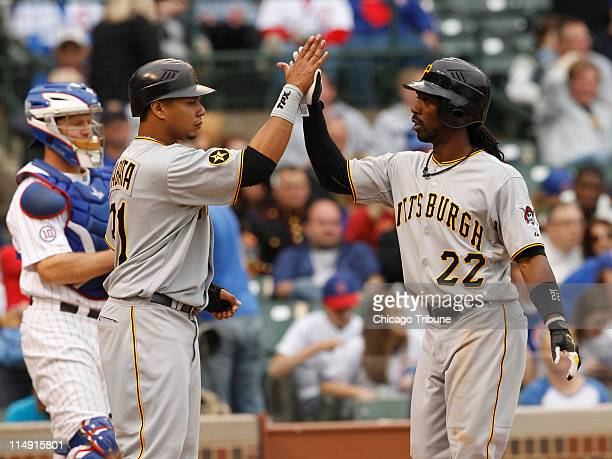 Chicago Cubs catcher Koyie Hill watches as the Pittsburgh Pirates Andrew McCutchen right is high fived by teammate Jose Tabata following his tworun...
