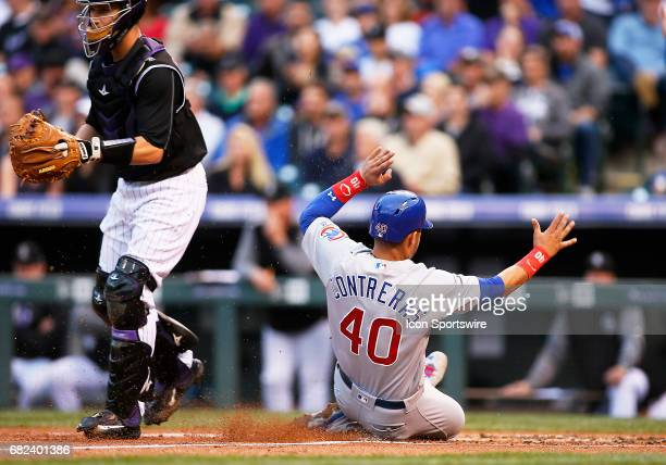 Chicago Cubs Catcher Willson Contreras slides safely into home plate as Colorado Rockies Catcher Dustin Garneau waits for the throw during a regular...