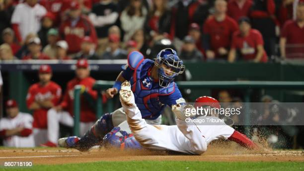 Chicago Cubs catcher Willson Contreras tags out the Washington Nationals' Trea Turner sliding at home plate in the first inning in Game 5 of the...