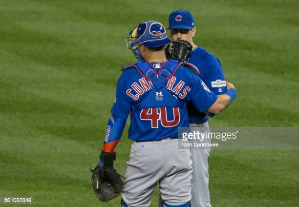 Chicago Cubs catcher Willson Contreras talks to starting pitcher Kyle Hendricks during game five of the NLDS between the Washington Nationals and the...