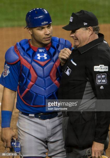 Chicago Cubs catcher Willson Contreras with umpire Jerry Layne after the umpire was hit in the face by a pitch during game five of the NLDS between...