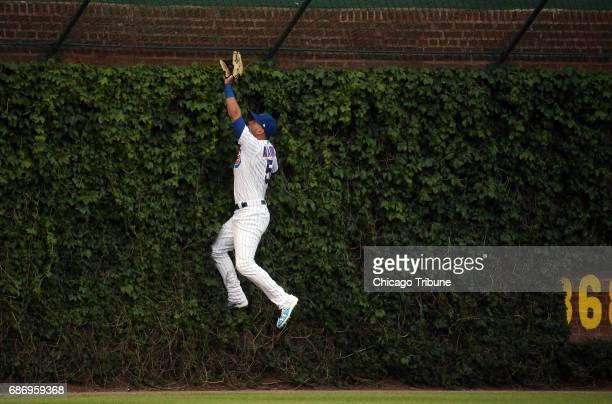 Chicago Cubs center fielder Albert Almora Jr climbs the ivy but can't catch a home run by San Francisco Giants second baseman Joe Panik in the first...