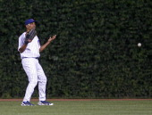 Chicago Cubs centerfielder Jacque Jones motions that he can't see the ball right coming from Philadelphia Phillies' Tadahito Iguchi who got a...