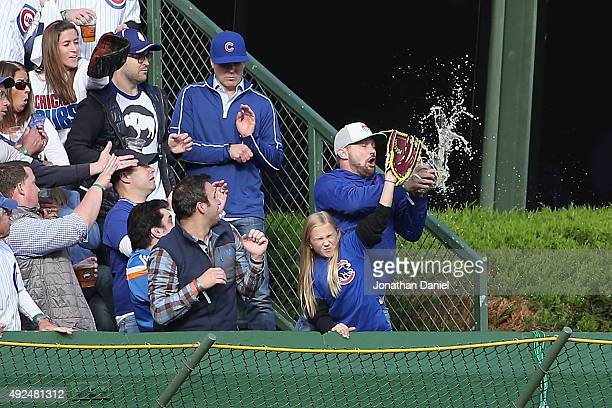 Chicago Cubs fan attempts to catch a home run ball hit by Stephen Piscotty of the St Louis Cardinals in the first inning during game four of the...