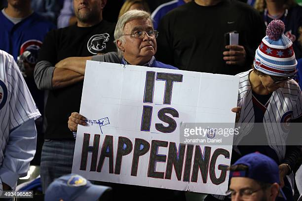 Chicago Cubs fan holds a sign that reads 'IT IS HAPPENING' prior to game three of the 2015 MLB National League Championship Series between the...