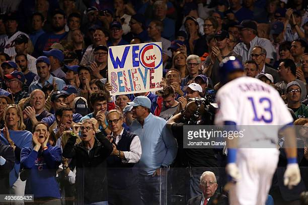 Chicago Cubs fan holds up a sign that reads 'We Believe' as Starlin Castro of the Chicago Cubs is up at bat against the New York Mets during game...