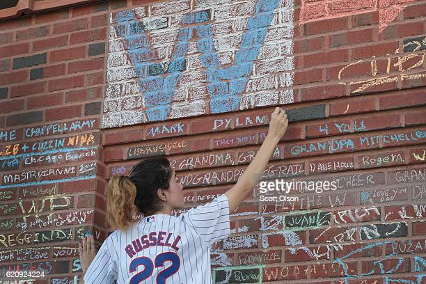 Chicago Cubs fan Rahaf Rihani chalks a message on a wall outside Wrigley Field the day after the Cubs defeated the Cleveland Indians to win the 2016...