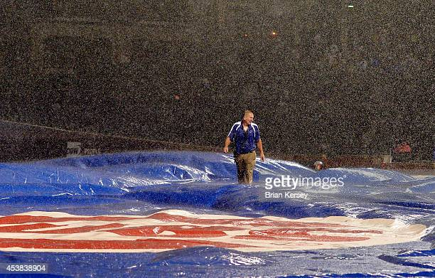 Chicago Cubs head groundskeeper Roger Baird walks across the field as his crew tries to get the tarp on the field during a downpour in the fifth...