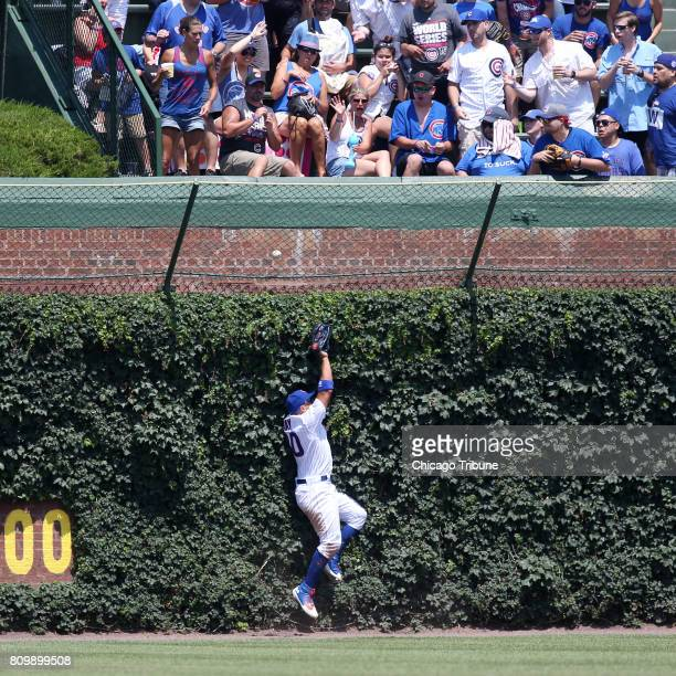 Chicago Cubs left fielder Jon Jay runs into the ivy while chasing a tworun home run ball hit by Milwaukee Brewers left fielder Ryan Braun in the...