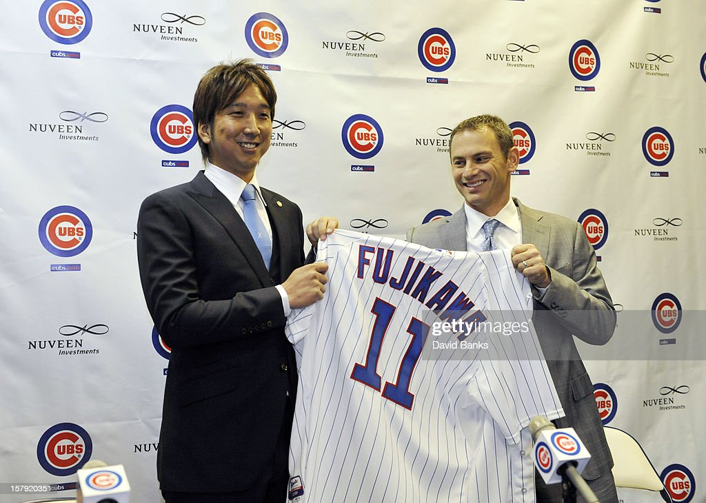 Chicago Cubs new pitcher Kyuji Fujikawa holds up his new jersey with Chicago Cubs general manager Jed Hoyer on December 7, 2012 at Wrigley Field in Chicago, Illinois.