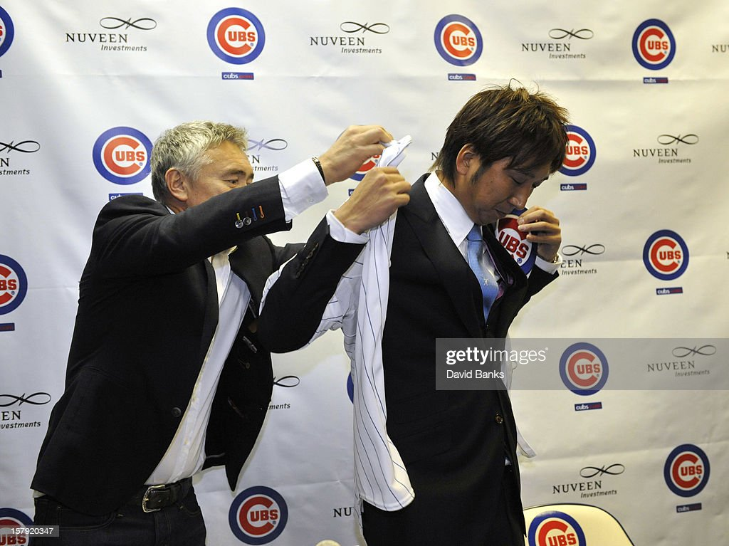 Chicago Cubs new pitcher Kyuji Fujikawa tries on his new jersey as he is introduced to the media on December 7, 2012 at Wrigley Field in Chicago, Illinois.