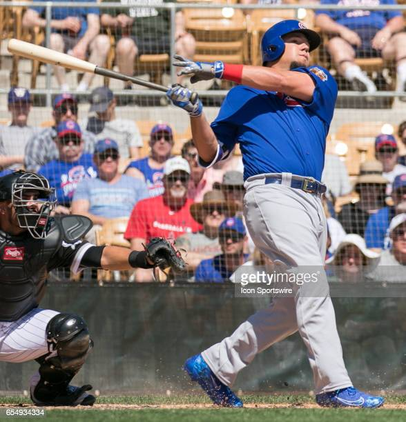 Chicago Cubs Outfielder Kyle Schwarber looks on as watches the baseball fly over the outfield wall for a home run during a spring training game...