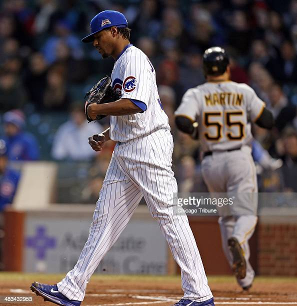 Chicago Cubs pitcher Edwin Jackson walks back to the mound as the Pittsburgh Pirates' Russell Martin scores on Travis Ishikawa's sacrifice fly the...