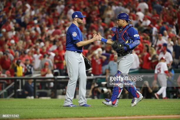 Chicago Cubs pitcher Wade Davis left and catcher Willson Contreras celebrate the final out in a 30 win against the Washington Nationals in Game 1 of...