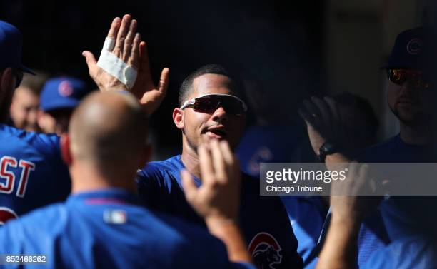 Chicago Cubs player Willson Contreras is congratulated in the dugout after scoring on a single by teammate Ian Happ in the second inning against the...