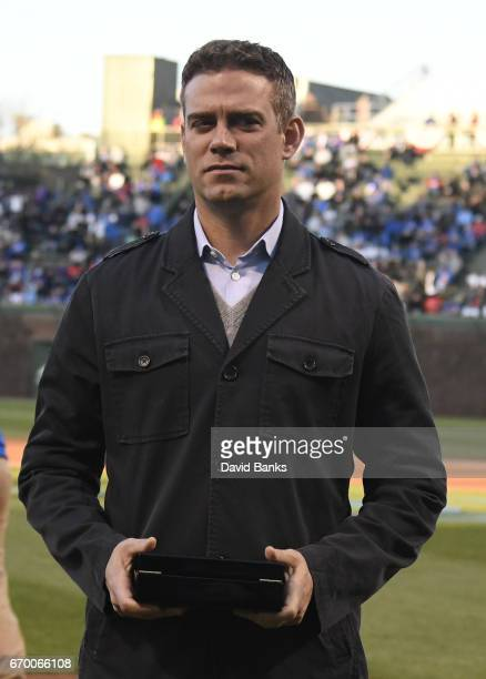 Chicago Cubs President Theo Epstein holds a 2016 World Series ring that he will present in a ceremony to former Cubs players before the game against...