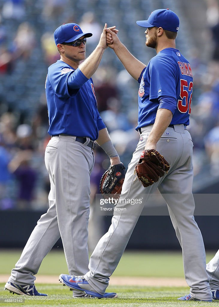 Chicago Cubs relief pitcher Justin Grimm high fives teammate Chris Valaika following the game against the Colorado Rockies at Coors Field on August 7...