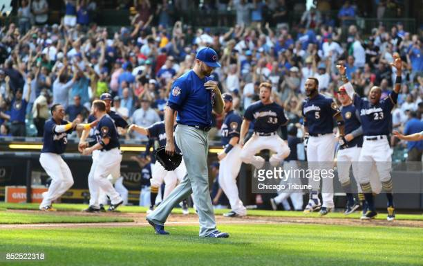 Chicago Cubs relief pitcher Wade Davis walks off the field as the Milwaukee Brewers celebrate their walk off home run in the 10th inning on Saturday...