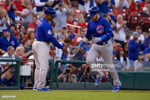 Chicago Cubs right fielder Ian Happ give a low five to Chicago Cubs third base coach Gary Jones after hitting a home run in the first inning against...