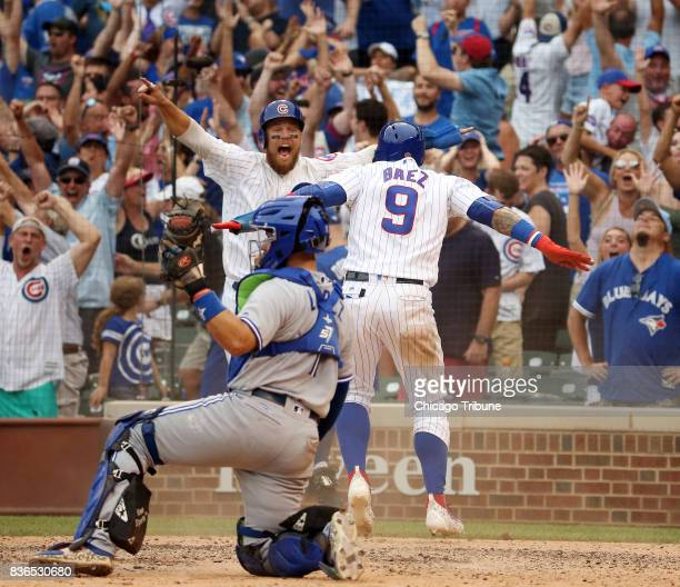 Chicago Cubs second baseman Ben Zobrist and Javier Baez celebrate as they score behind Toronto Blue Jays catcher Raffy Lopez in the 10th inning for a...
