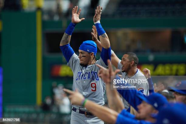 Chicago Cubs second baseman Javier Baez raises his arms in celebration after catcher Alex Avila triples and center fielder Leonys Martin scores...