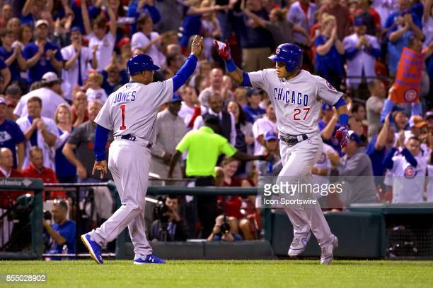 Chicago Cubs shortstop Addison Russell gives Chicago Cubs third base coach Gary Jones a high five after hitting a home run in the top of the 7th...