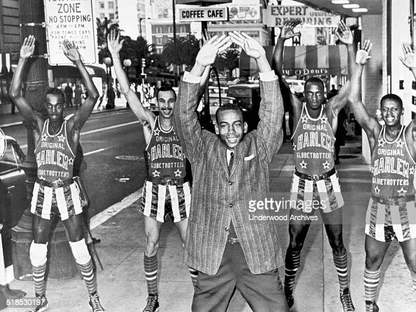 Chicago Cubs shortstop Ernie Banks leads members of the Harlem Globe Trotters in calisthenics on a downtown street San Francisco California January...