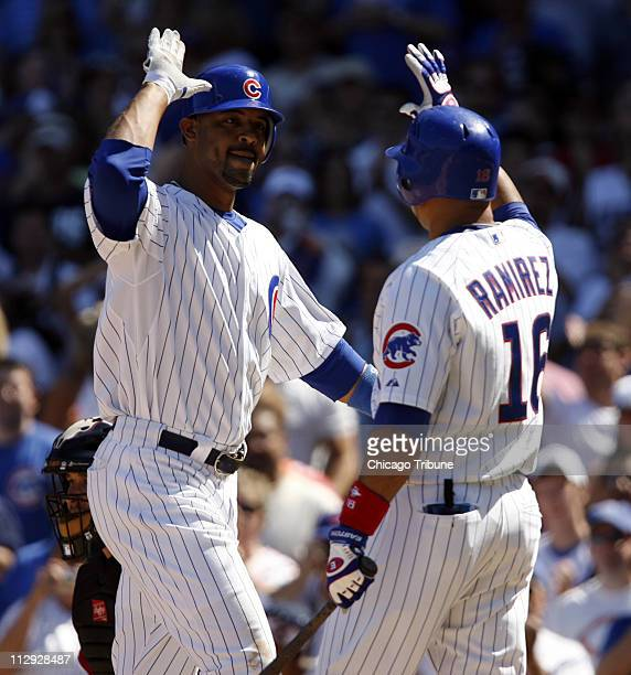 Chicago Cubs slugger Derrek left is congratulated by teammate Aramis Ramirez after Lee hit a home run to lead off the eighth inning against the...