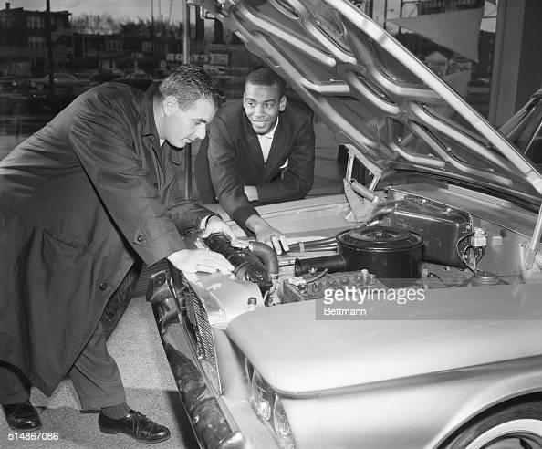 Chicago Cubs' star shortstop Ernie Banks working in the offseason as a car salesman looks under the hood of a car with a customer Chicago November 4...