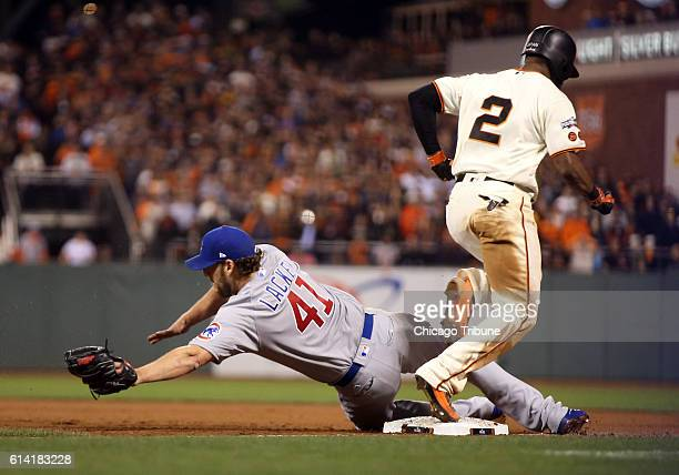 Chicago Cubs starting pitcher John Lackey dives but can't force San Francisco Giants center fielder Denard Span out at first base allowing a run to...